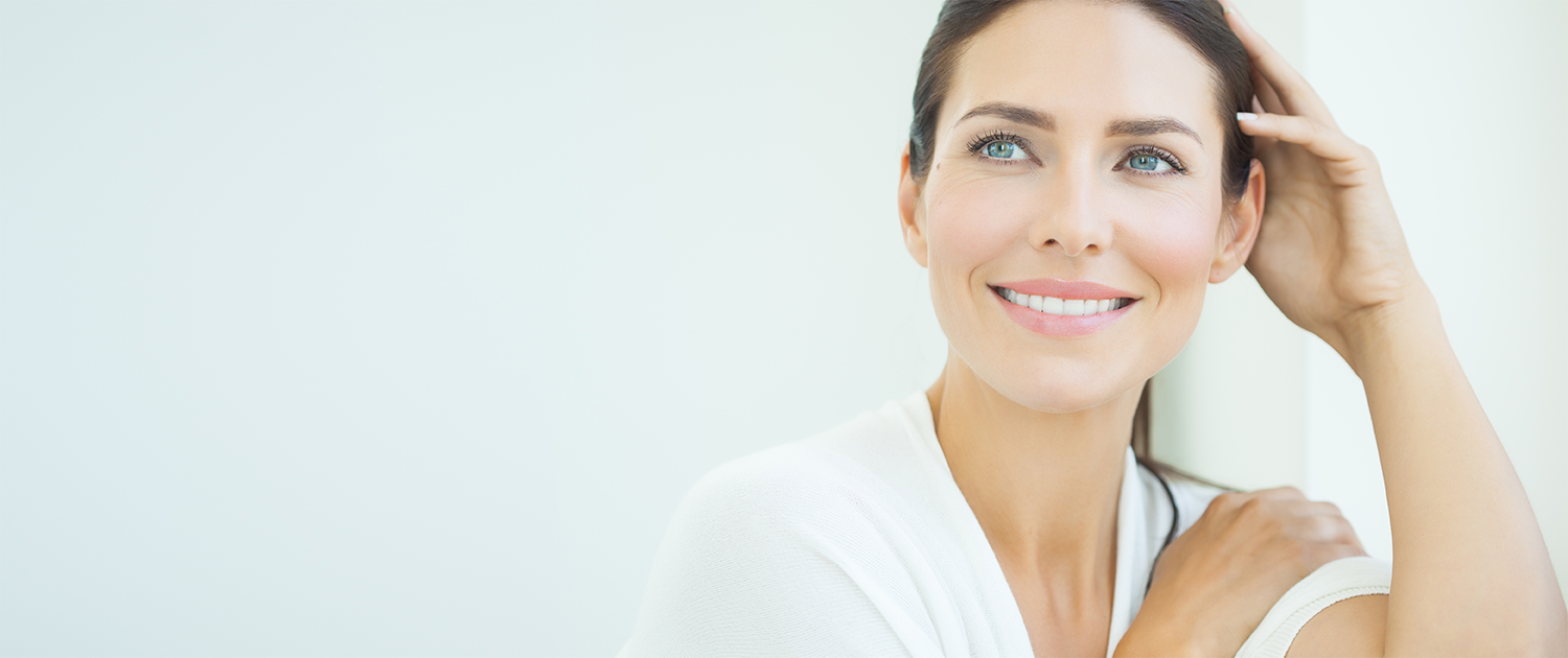 Woman smiles showing off her Invisalign aligner from BRO