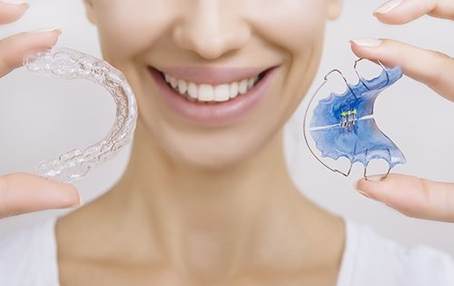 Woman holds up her retainer and Invisalign aligner