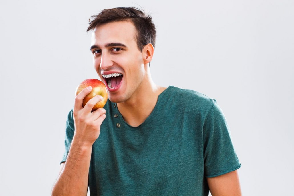 Man with braces snacking on an apple in Western North Carolina