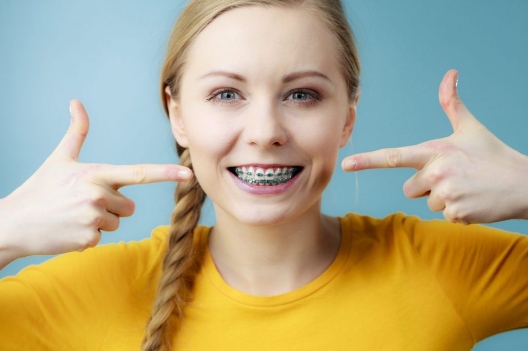 Woman with braces covered by dental insurance
